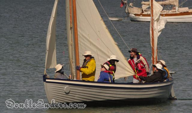 White double-ended open vessel under sail with seven people aboard